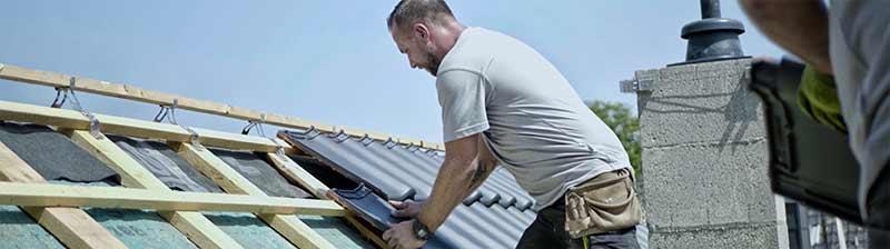neues Dach - Profis vor Ort: Dachdecker auf dem Dach beim Eindecken mit Dachziegeln